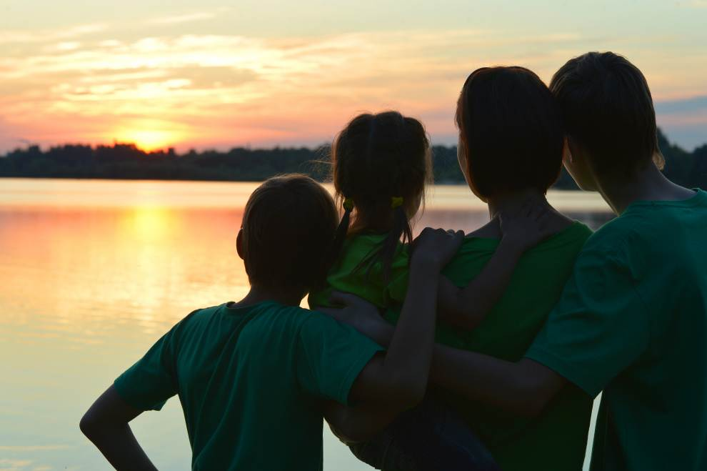 Family Watching Sunset Over Lake